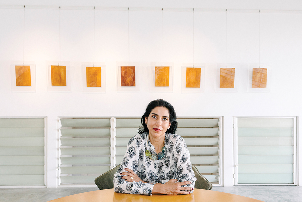 Shalini Ganendra, founder of SGFA, backed by a row of works from Bibi Chew.