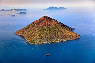 An aerial view of northeastern Stromboli, with the islands of Panarea, Salina, Lipari, Vulcano, and Filicudi in the background.