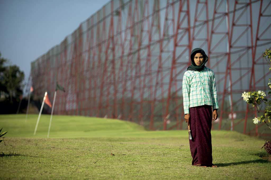 A gardener at the City Golf course in Naypyidtaw is photographed beside the netting of the driving range.