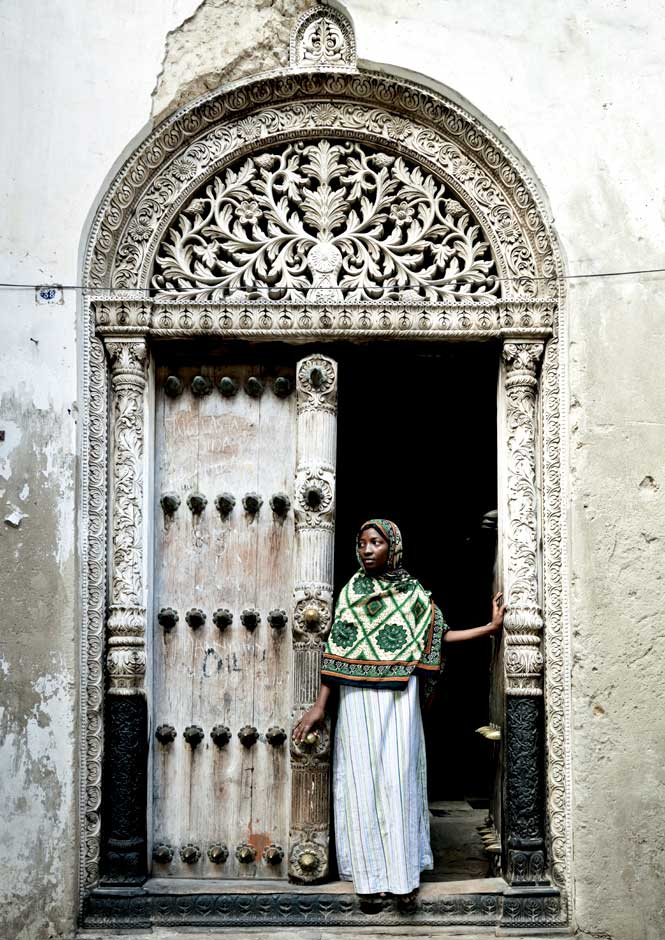 A swahili woman framed by one of stone town's intricately carved doorways.