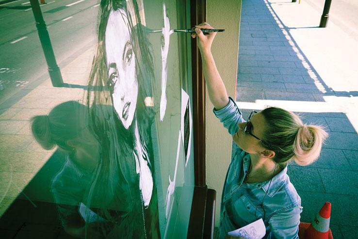 Artist Pip McManus works on her 140 ART display.