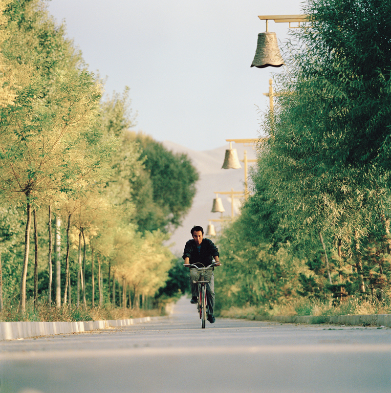 Pedaling down a qauiet Dunhuang road.