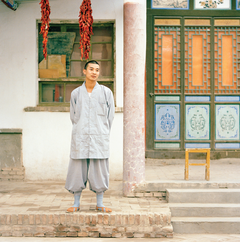 A young buddhist monk outside a temple in Dunhuang.