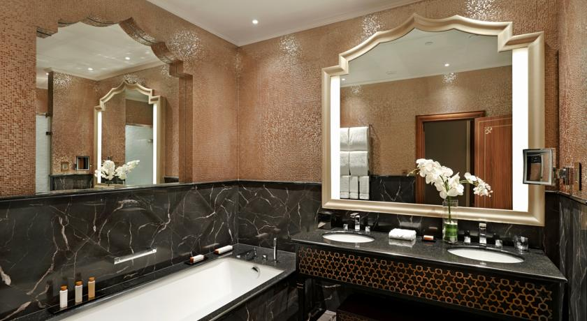 The bathrooms in the King Tower Suite features marble features, a rain shower, and an in-mirror TV.