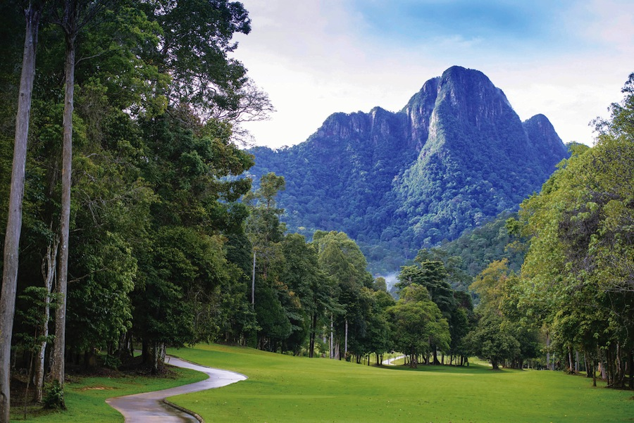 A forest-flanked fairway at Langkawi's Els Club Teluk Datai, with Mount Mat Cincang in the background.