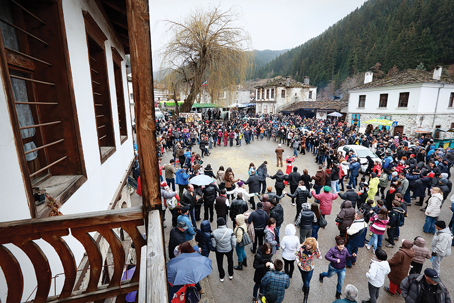 Crowds descend on Shiroka Laka's main street to take in the Kukeri festivities.