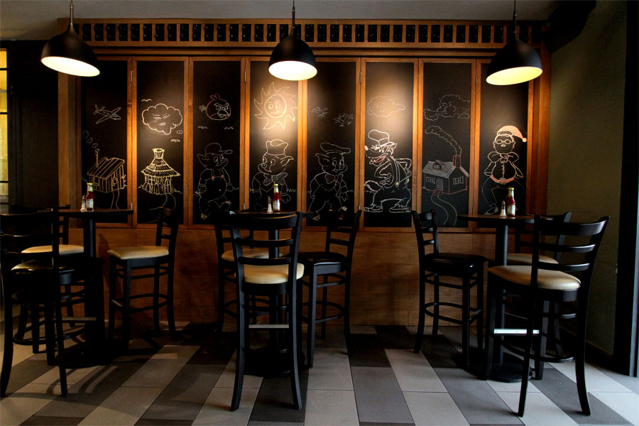 Chalkboards pull back to reveal the extensive wine collection at the Three Little Pigs.