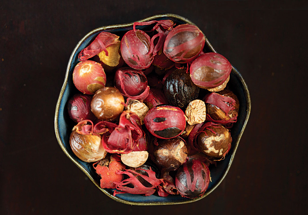A bowlful of nutmeg seeds, some still covered in the scarlet membrane that yields mace.
