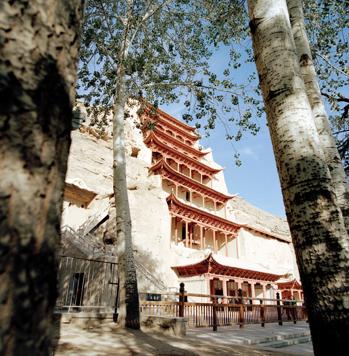 A temple facade at Mogao Caves is set directly into the sandstone cliff face.