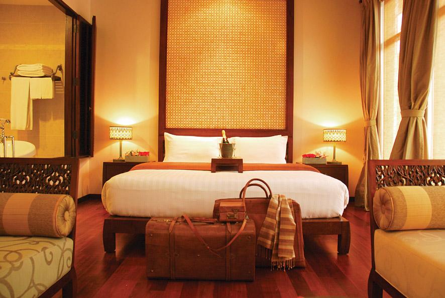 Room features include hardwood floors, apsara sculptures, and balconies that overlook the central courtyard's saltwater pool.