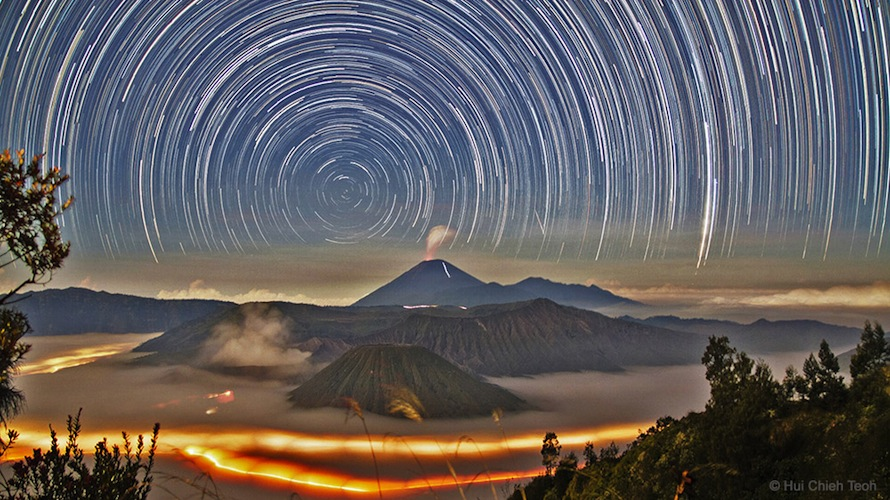 'Star Trails over Bromo' by Hui Chieh Teoh of Malaysia (www.mydarksky.org). Time-exposure image of star trails around the south celestial pole, above volcanoes in the Bromo Tengger Semeru National Park of East Java, Indonesia. Lit by the rising moon, Mt. Bromo is the steaming crater in the center, June 2014. The 4th winner in the Against the Lights category.