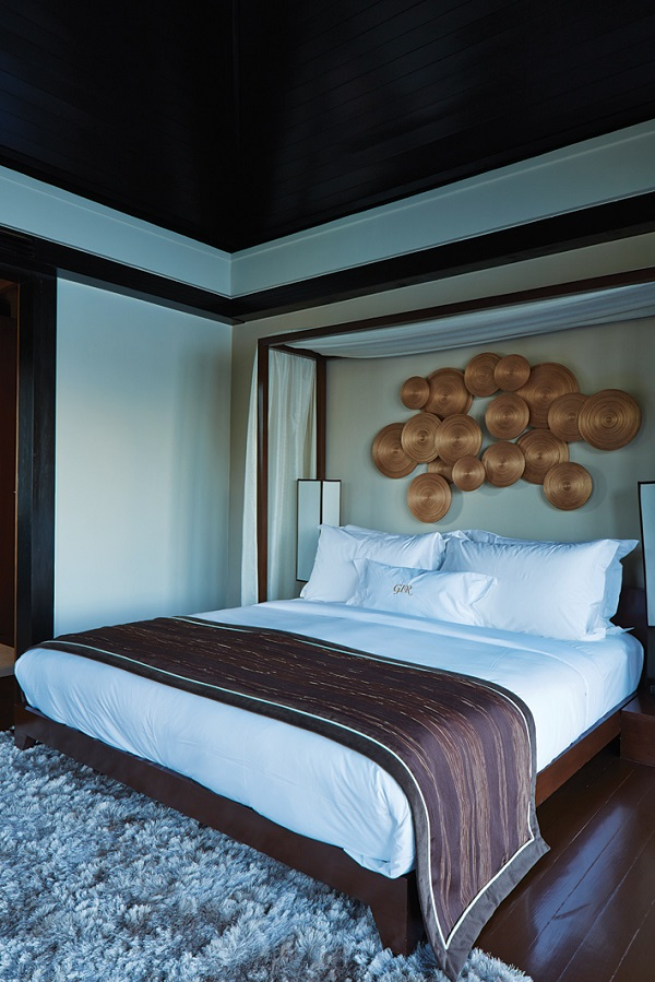 Suite bedrooms feature brass wall art and batik throws.
