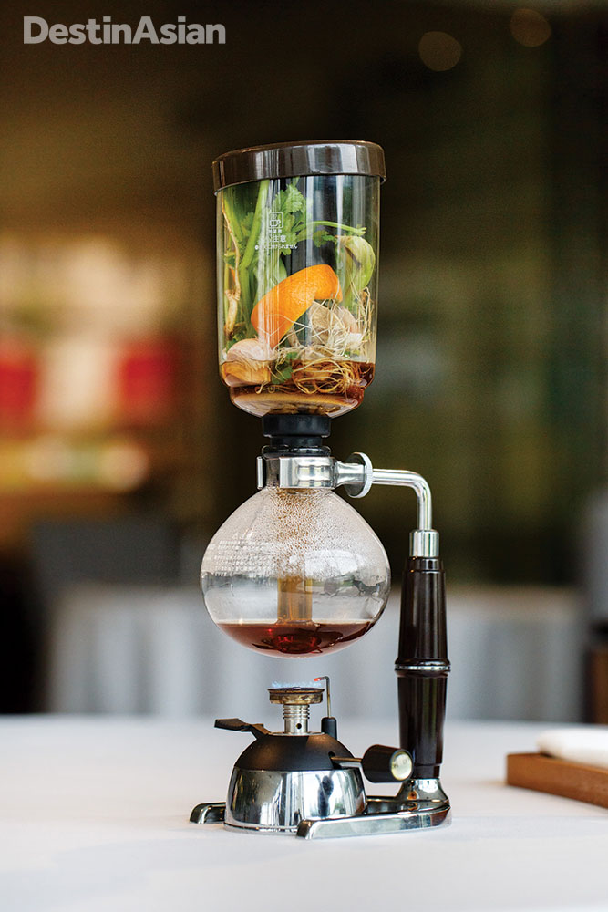 An infusion siphon preparing a broth tableside.