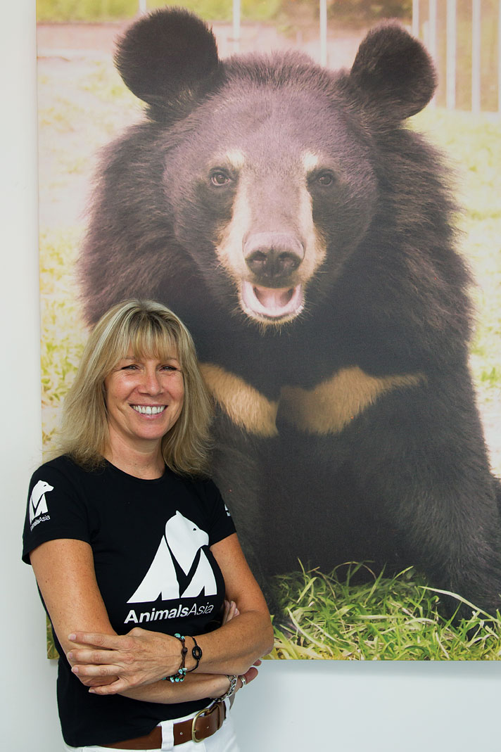 Jill Robinson at Animals Asia's Hong Kong office standing next to a picture of Jasper, a rescued moon bear.