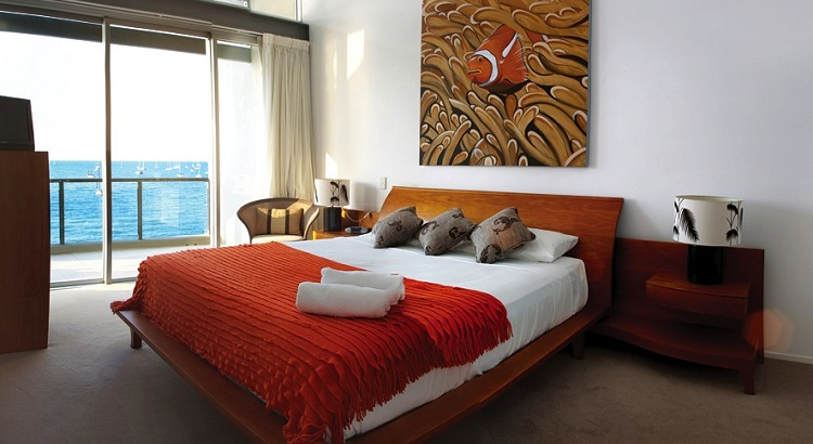 An apartment bedroom at the Peninsula Airlie Beach.