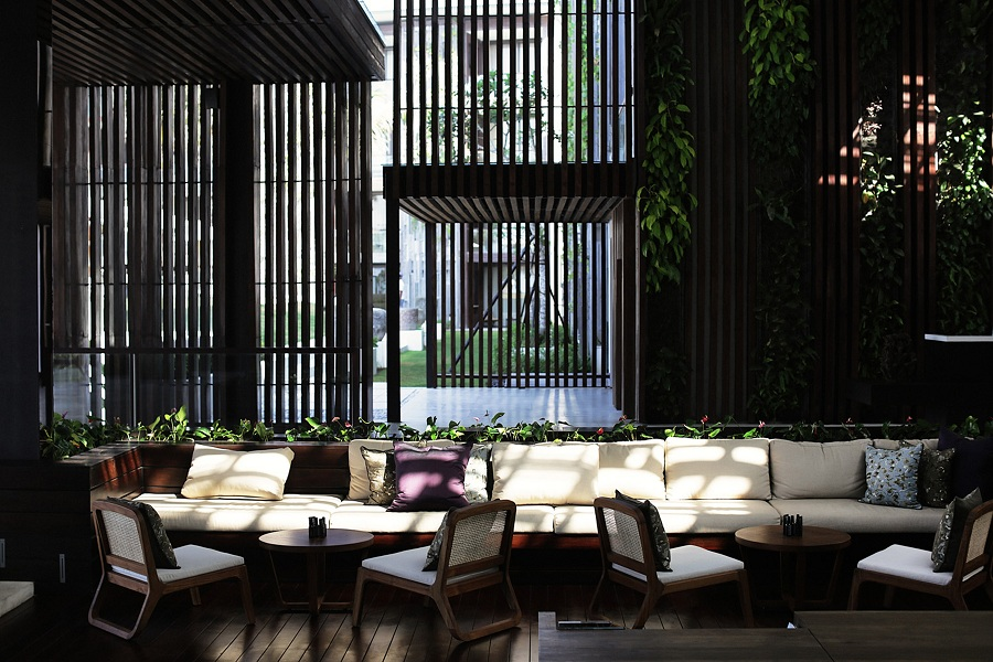 Sun floods through wood panels in the open-air lobby.
