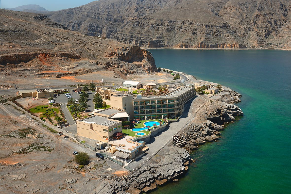 The Atana Khasab hotel sits perched atop a rocky cliff overlooking the sea.