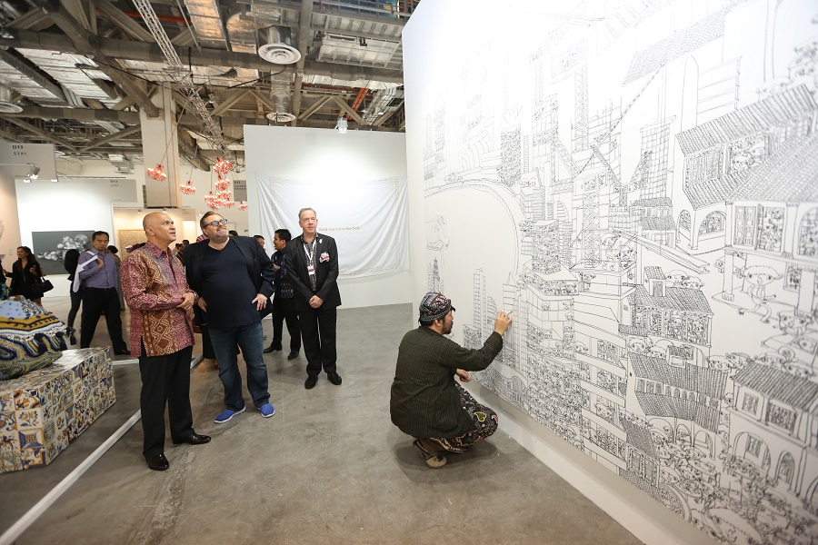Artist Shintaro Miyake does a live-art exhibition at the Tomio Koyama Gallery booth as Rudolf and the Indonesian ambassador to Singapore, His Exellency Dr. Andri Hadi, left, watch.