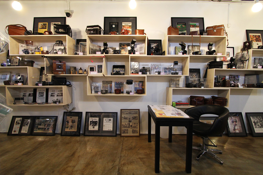 Personal photos, vintage lenses, and collectable cameras deck the insides of Bang Bang Geng.