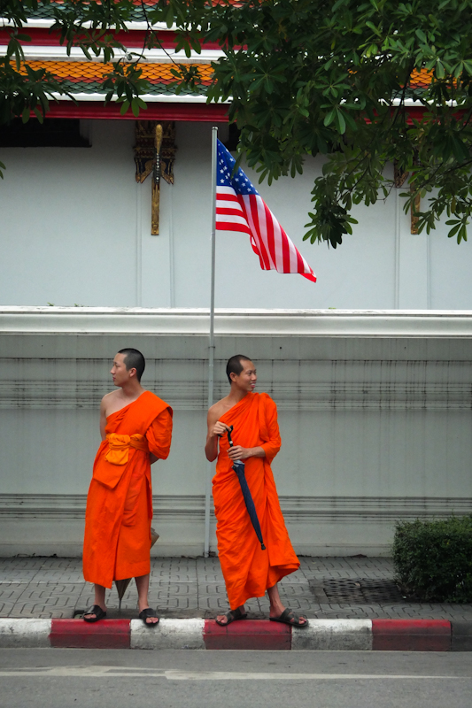 Two monks idle street-side in the world's most visited city.