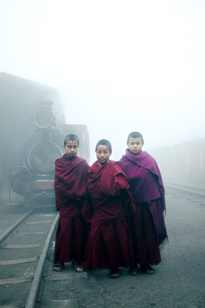 Novice monks posing in front of a vintage steam engine in Darjeeling, West Bengal.