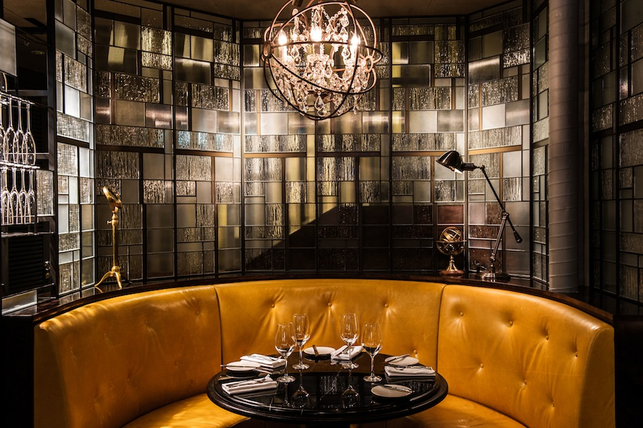 Tufted banquettes, industrial-chic chandeliers, and a predominately black color palette are themes throughout.