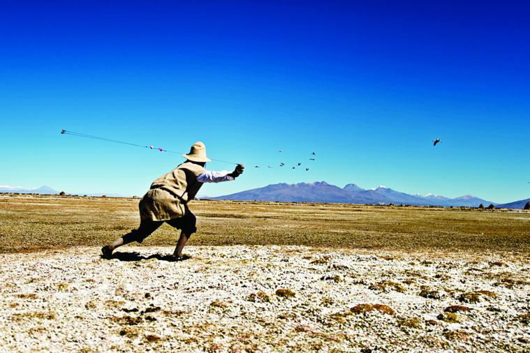 As a low flying flock of flamingos approaches, Jose Luis Mamani Chino leaps to his feet and swings his sconi throwing weapon - versions of which are used throughout the Andes.