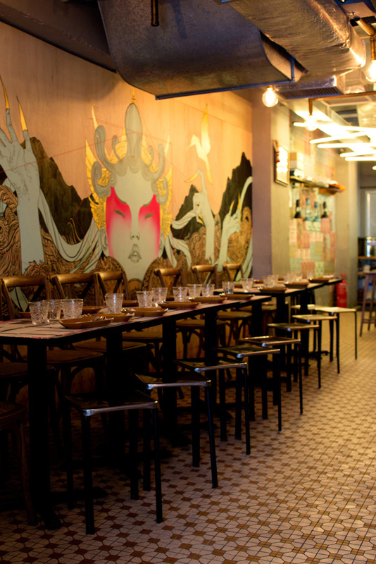 Leather banquettes line a distressed, graffitied concrete wall at Fatty Crab.