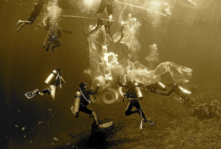Divers sinking the Apsara - a sculpture inspired by Hindu goddesses - at Jemeluk Bay,