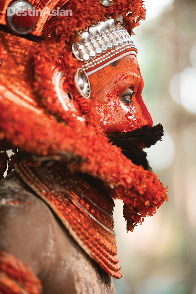 A Theyyam performer in profile.