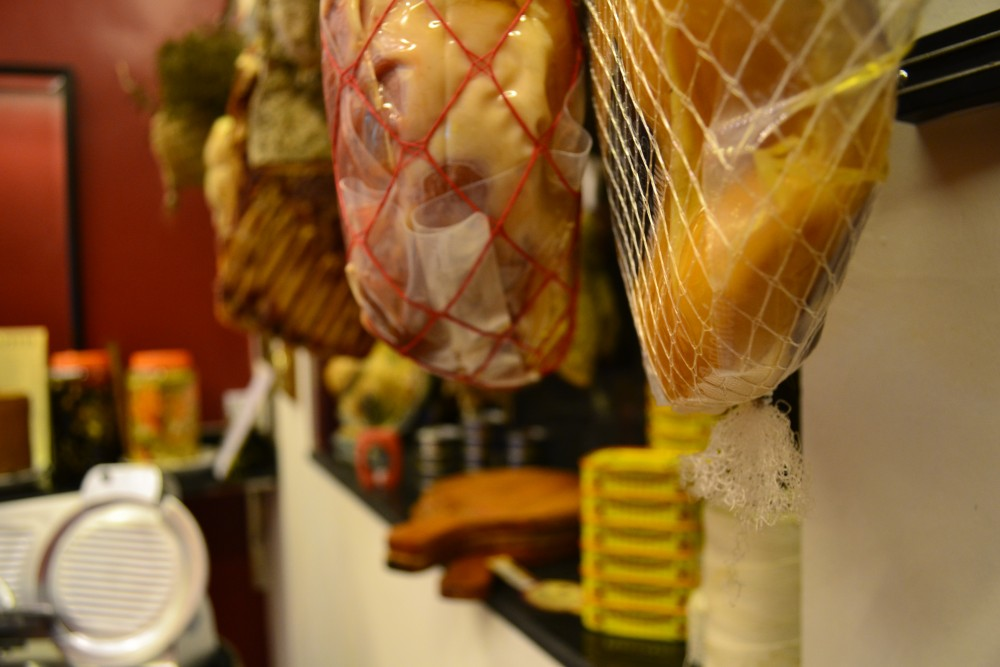 Cured meats hang from the ceiling inside.