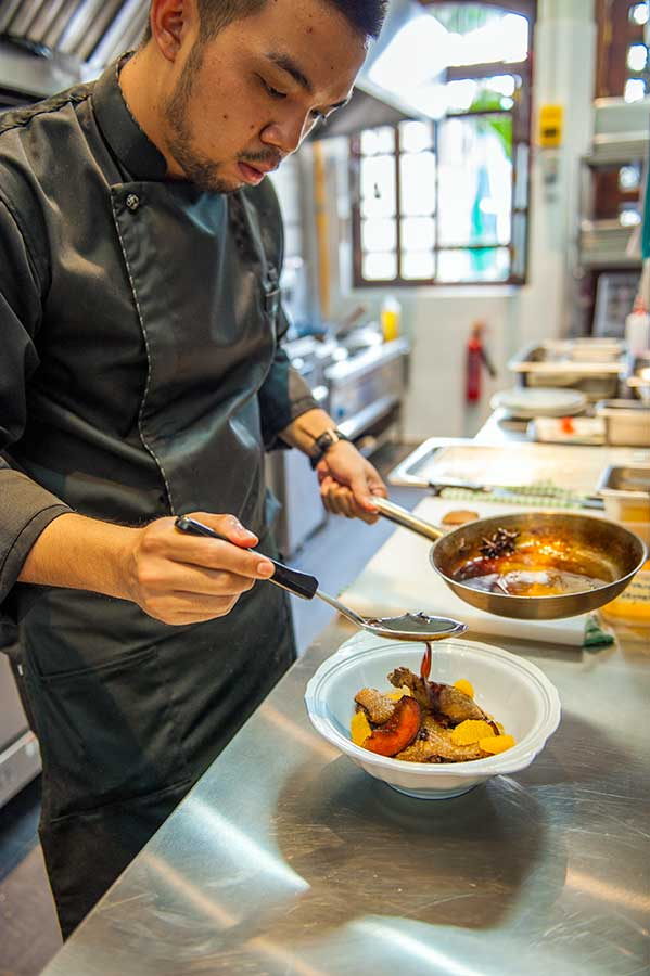 Chef Zachary Choong preparing a serving of Five-Star Duck.