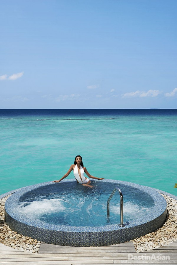Taking a dip in the Jacuzzi at Velaa Private Island's overwater spa. (Swimsuit by Aqua De Alma)