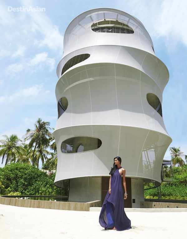 At the base of the resort's 11-meter-high tower, which houses Tavaru restaurant and a well-stocked wine cellar. (Dress by Halston Heritage; silver bangle by John Hardy)