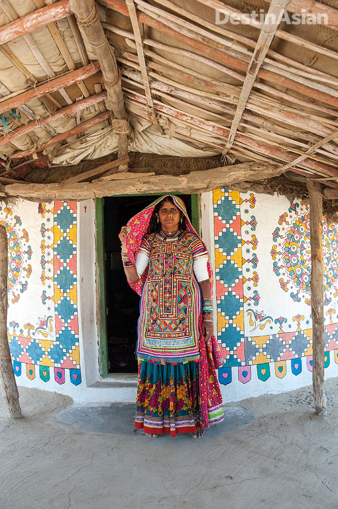 A meghwal tribal woman standing in front of her family's ornately painted bhunga - a conical mud-brick hut - in the village of Hodka.