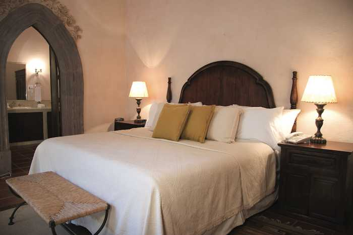 A Deluxe Room with dark wood accents and colonial stucco walls.