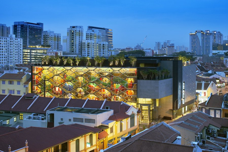 Greg Shand Architects designed the building to mimic the colors of Little India's shophouses by day and glow like a lantern at night.