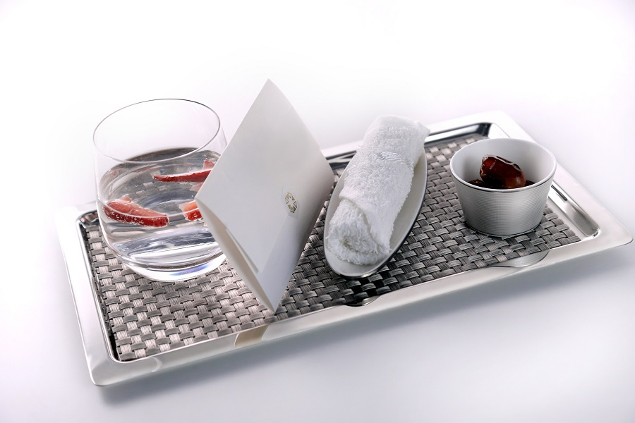 First-class fliers are greeted with a welcome note, drink, hot towel, and Arab dates.