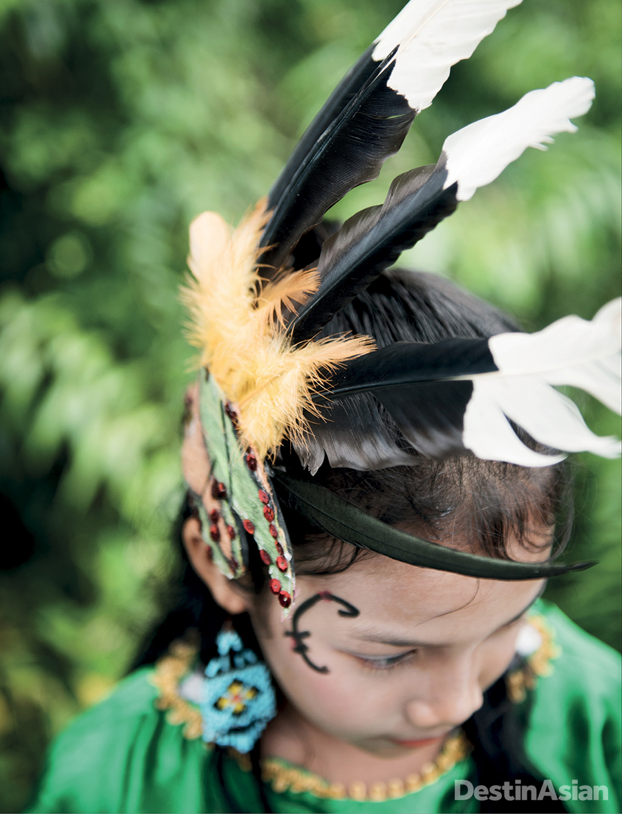 A young dancer in Bukitrawi village sports a hornbill-inspired headdress.
