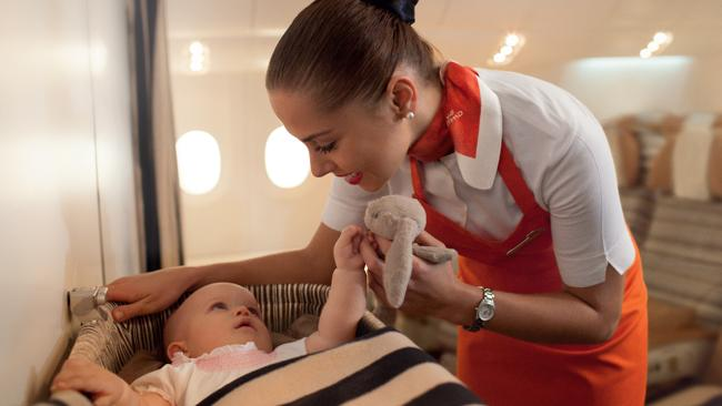 Flying nannies wear bright orange aprons onboard.