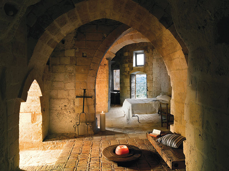 Arched and vaulted, the two-bedroom Cave 21 suite at Sextianto Le Grotte Della Civita comes with a private terrace overlooking Matera's rocky terrain.