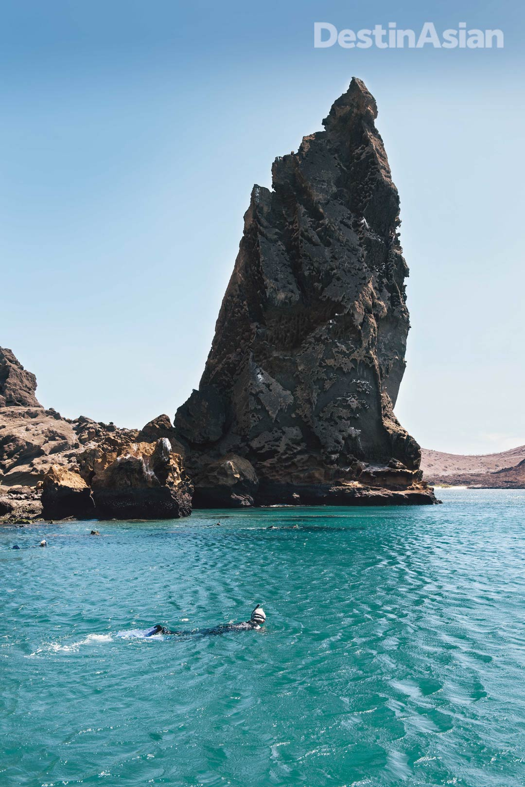 Snorkelers braving the cold waters off Bartolomé Island's iconic Pinnacle Rock.