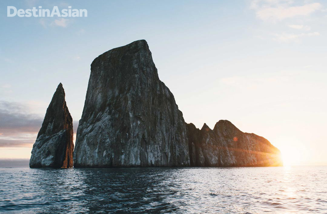 The sun setting behind Kicker Rock off San Cristóbal. The remnant of a volcanic cone, this iconic formation is also known by the Spanish name León Dormido because it resembles a sleeping lion when viewed from the south.