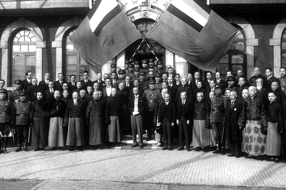 Puyi (center) posing with a group of dignitaries and officials, circa 1938.