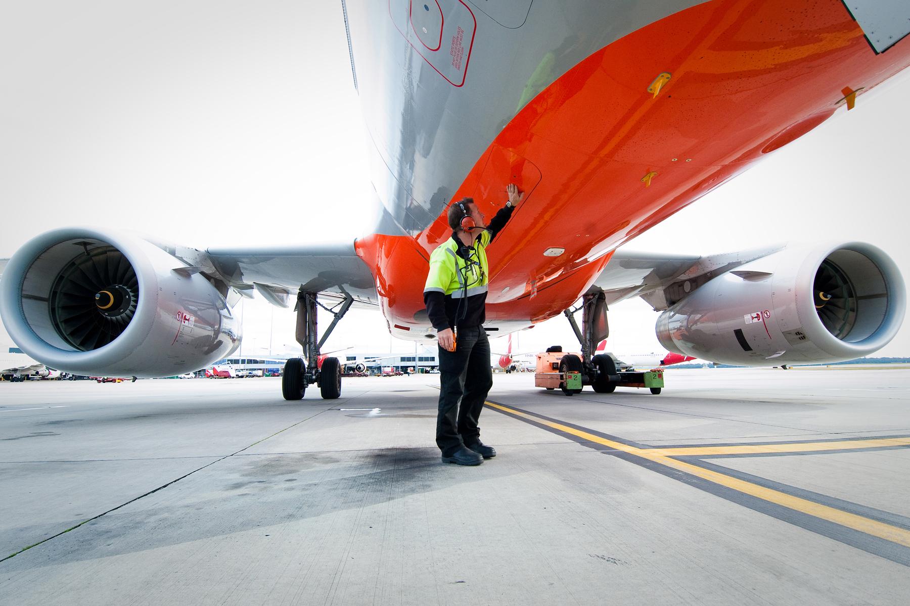 Ground staff directing a Jetstar plane.