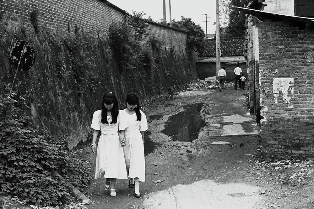 An eerie photo of two young girls in Shilong, Guangdong by Han Lei.
