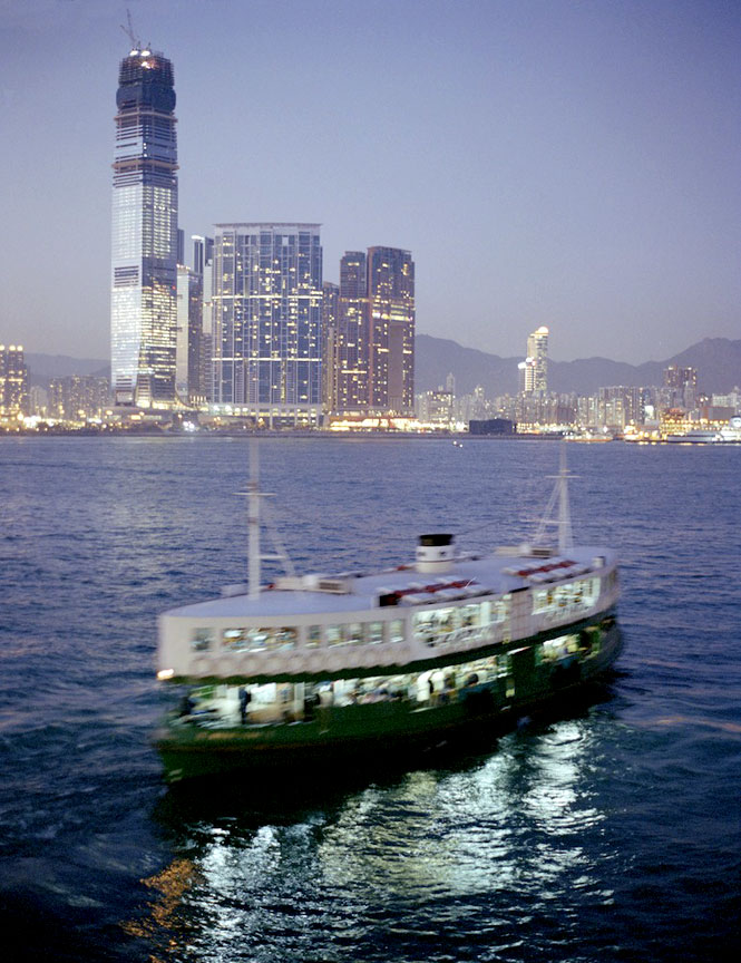 The skyscrapers of the West Kowloon reclamation area tower over a Star Ferry on Victoria Harbour.