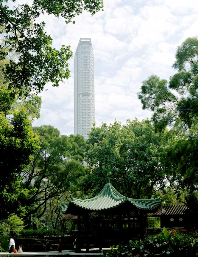 A skyscraper towers over the greenery of Kowloon Park.