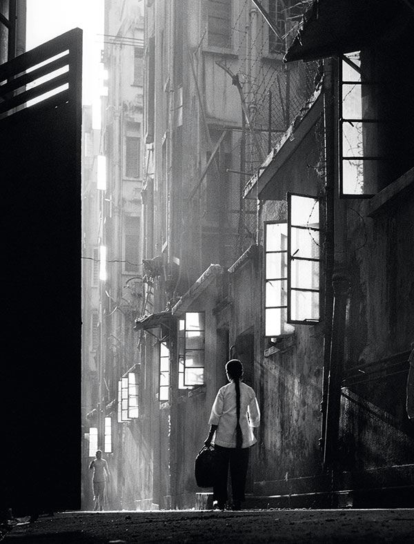 Fan Ho's work often portrays solitary figures, as in this image, Back Lane.