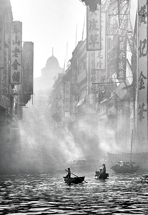 Sampans along the hazy Victoria Harbor waterfront, as pictured in Dream of Old Hong Kong, an image shot by Fan Ho in 1957.